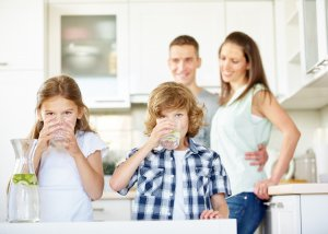 Family drinking water in a health and wellness coaching article presenting 2 simple ways to have better skin